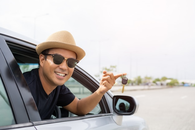 車の中で彼のキーを取得する若いアジア人。レンタカーまたは購入車の概念。