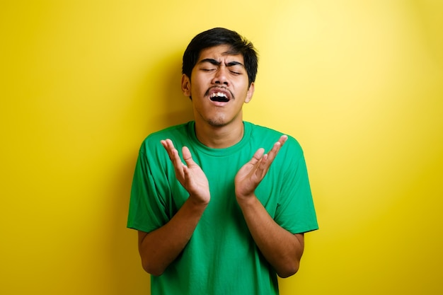 Young asian man in green t-shir close his eyes while rise his arm in front his chest looks sad, loosing failure gesture against yellow background
