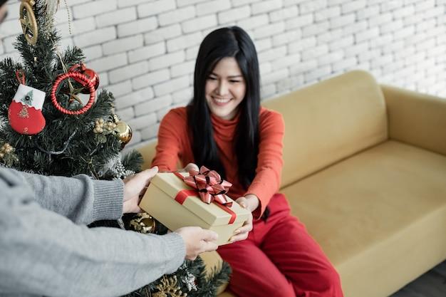 若いアジア人男性は、コピースペースのある自宅でクリスマスにガールフレンドにギフトボックスを手渡しました。クリスマスに彼氏からギフトボックスを受け取るアジアの女の子。