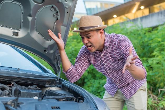 彼の車に問題がある若いアジア人