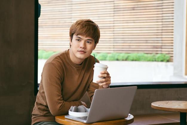 一杯のコーヒー、コーヒーの時間と夏休みの休暇の概念を保持している若いアジア人