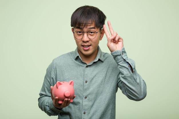 돼지 저금통을 들고 젊은 아시아 남자 재미와 승리의 제스처를 하 고 행복