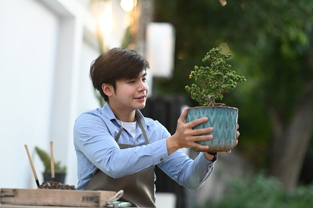 A young asian man holding bonsai tree pot while sitting at his home garden .