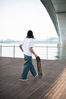 彼のスケートボードを保持している若いアジア人