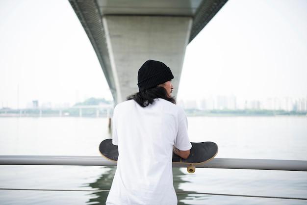 그의 스케이트 보드를 들고 젊은 아시아 남자