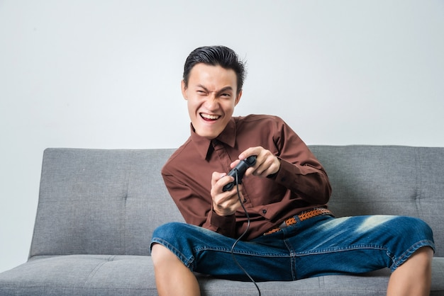 Young asian man holding joystick for playing soccer video game while sitting on sofa in living room.