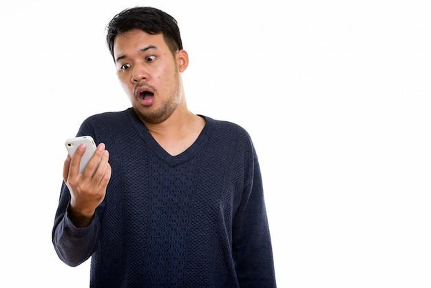 그의 mobie 전화를 보면서 휴대 전화를 들고 젊은 아시아 남자