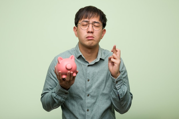 Young asian man holding a piggy bank crossing fingers for having luck