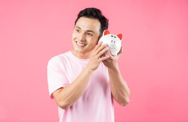 핑크에 돼지 저금통을 들고 젊은 아시아 남자