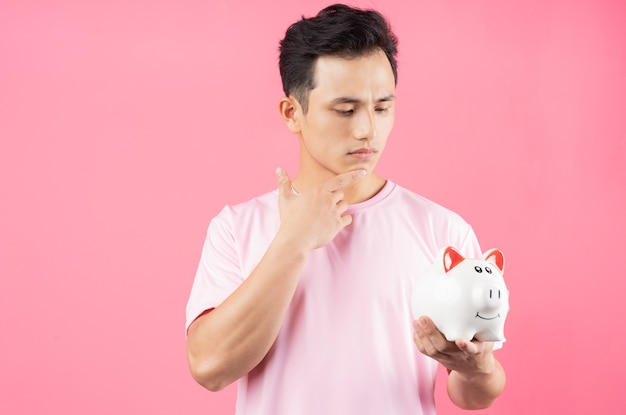 Young asian man holding piggy bank on pink
