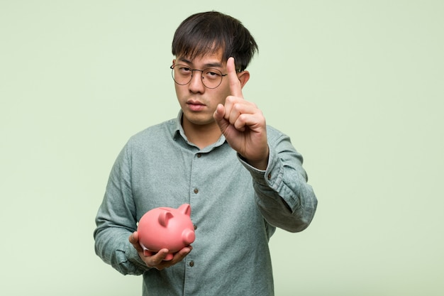 Young asian man holding a piggy bank showing number one