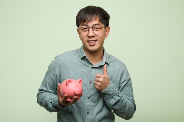 Young asian man holding a piggy bank smiling and raising thumb up
