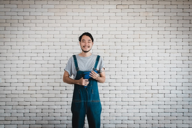 Young asian man holding power drill standing in front of white brick wall, smiling