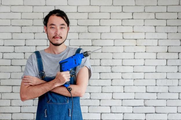白いレンガの壁の前に立って、笑顔でカメラを見て、電動ドリルを持っている若いアジア人男性、ホームdiyのコンセプト
