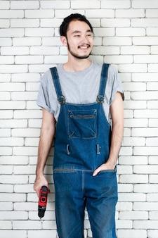 白いレンガの壁の前に立って、笑顔で見ている電動ドリルを保持している若いアジア人男性