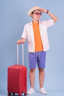 青い背景に赤いスーツケースを保持している若いアジア人男性