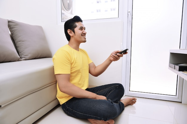 Young asian man holding remote control watching tv while sitting