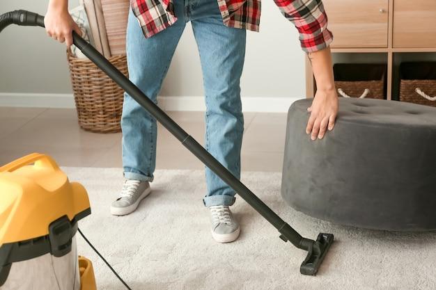 若いアジア人男性が自宅の床をフーバリング