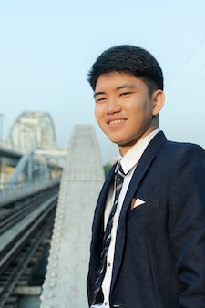 Молодой азиатский мужчина в костюме улыбается и стоит на мосту