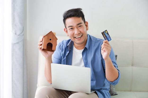 ラップトップコンピューターとクレジットカードとリビングルームで家の概念のための銀行ローンを示す小さな家モデルと青いシャツの若いアジア男