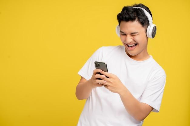 カジュアルな服装の若いアジア人男性は、ワイヤレスヘッドホンを聞いて喜んでいます。彼は黄色の背景で彼のスマートフォンで歌を聞いています。
