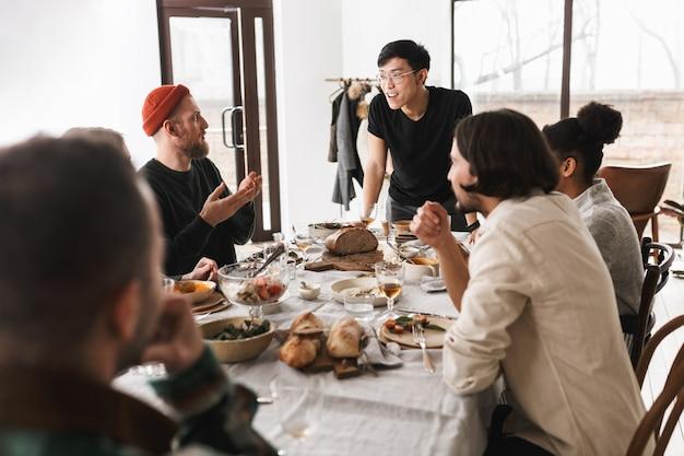 Молодой азиатский мужчина в очках и черной футболке, опираясь на стол, радостно разговаривает с коллегами