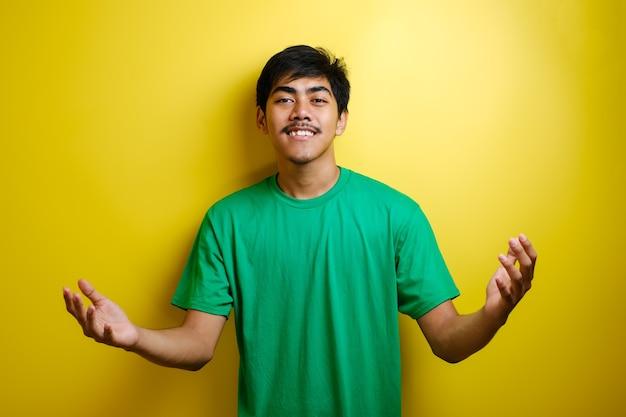 緑のtシャツの笑顔と黄色の背景に対して歓迎のジェスチャーを示す若いアジア人男性