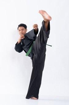 プンチャックシラットの制服を着た若いアジア人男性が両方の拳の動きを前に蹴ります