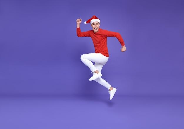 紫色の壁にサンタの帽子のジャンプと笑顔の顔を身に着けている赤いカジュアルな服装の若いアジア人男性。明けましておめでとうございます。