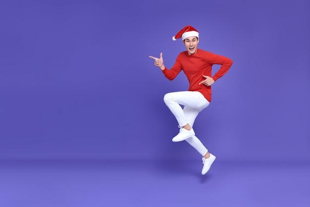 人差し指を脇に置いてジャンプする赤いカジュアルな服装の若いアジア人男性は、紫色の壁にコピースペースと笑顔の顔をしています。新年あけましておめでとうございます。
