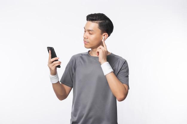 Молодой азиатский человек в обмундировании спорта держа smartphone и слушая музыку с счастливым лицом изолированный