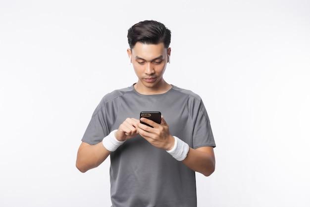 Молодой азиатский человек в спортивных костюмах играя телефон и слушая музыку при счастливое лицо изолированное на белой стене