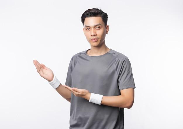Молодой азиатский человек в обмундировании спорта указывая к copyspace и смотря к камере изолированной на белой стене