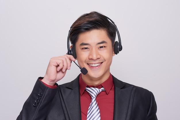 헤드셋을 쓰고 양복을 입은 젊은 아시아 남자
