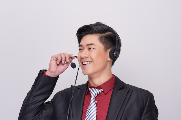ヘッドセットを身に着けているスーツの若いアジア人