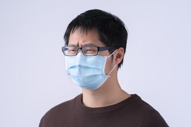 若いアジア人男性は咳をしていて、気分が悪く、白い背景に隔離された医療用の青いフェイスマスクを着用して嘔吐し、クローズアップ、スペースをコピーします。