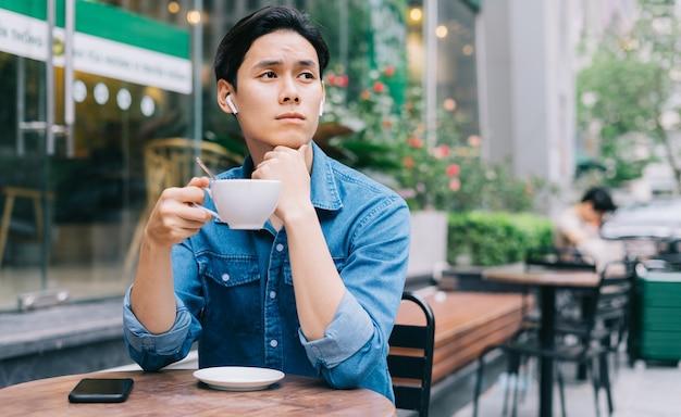 Молодой азиатский мужчина задумчиво сидит, попивая кофе