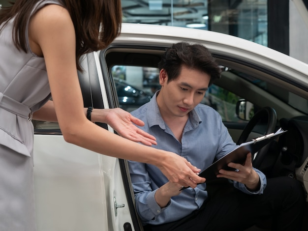 Young asian man is talking to sales manager while choosing a car in dealership.
