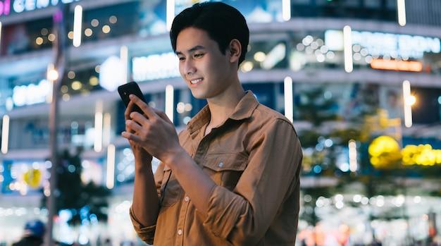 Молодой азиатский мужчина использует свой телефон во время прогулки по улице ночью