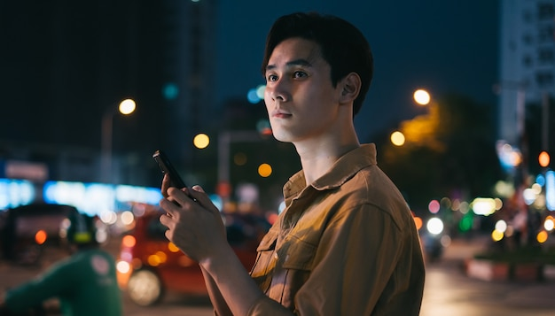 Young asian man is using his phone while walking in the street at night