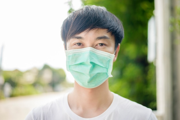 Young asian man is wearing face mask in city outdoor