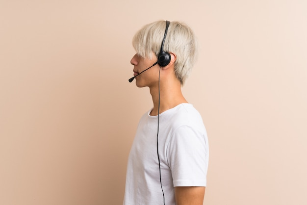 Young asian man over isolated  working with headset