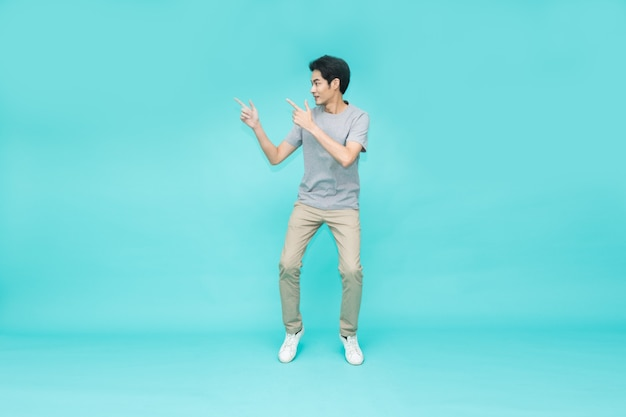 Молодой азиатский мужчина прыгает и указывает на пустое пространство для копирования, изолированное на зеленом фоне