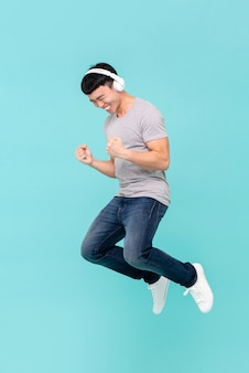Young asian man jumping happily listening to music