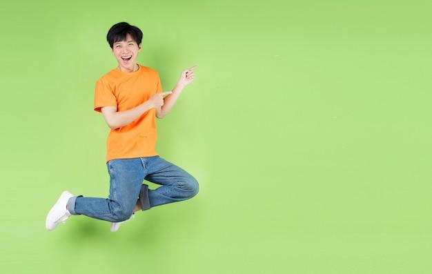 Молодой азиатский человек прыгает, изолированные на зеленом фоне