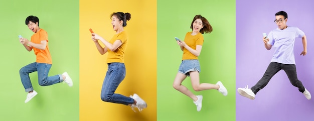 Молодой азиатский мужчина прыгает на зеленом фоне
