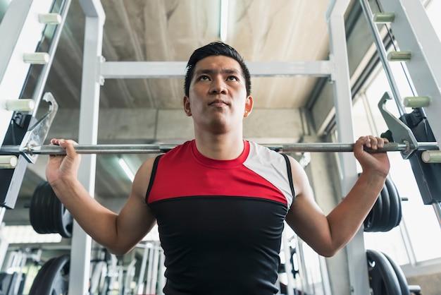 Штанга молодого азиатского человека поднимаясь в спортзале. здоровый образ жизни и концепция мотивации тренировки.
