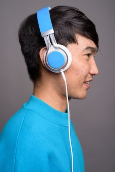 Young asian man listening to music against gray wall