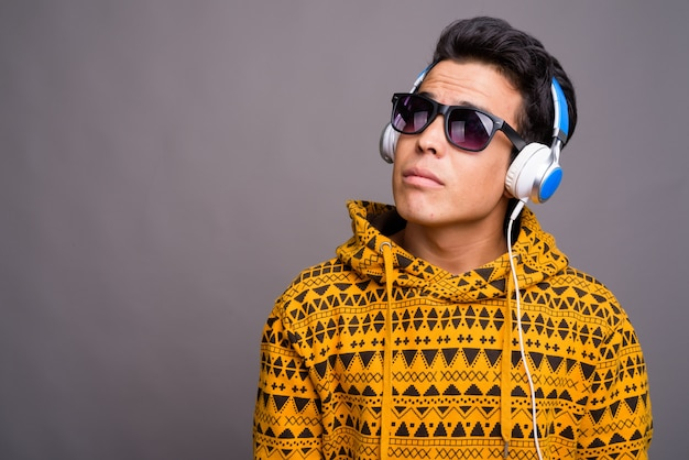 Young asian man listening to music while wearing hoodie against gray wall