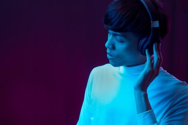 Музыка молодого азиатского человека слушая с наушниками в неоновом свете.